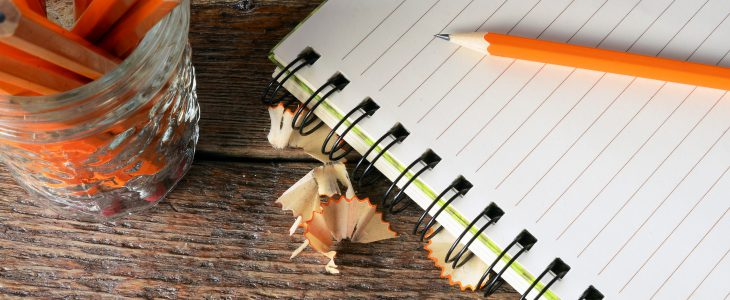 A top view image of an open notebook, lesson plan and several wooden pencils.